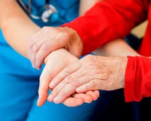 nurse helping senior to standup