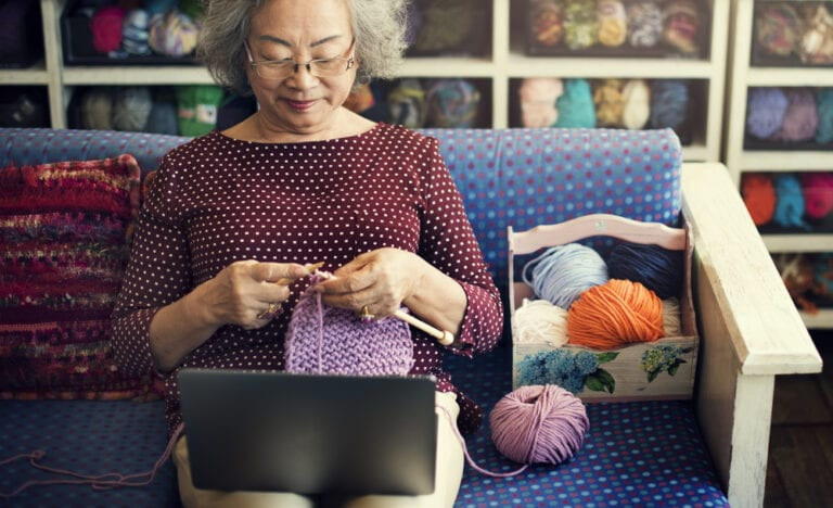 Senior woman crocheting at home