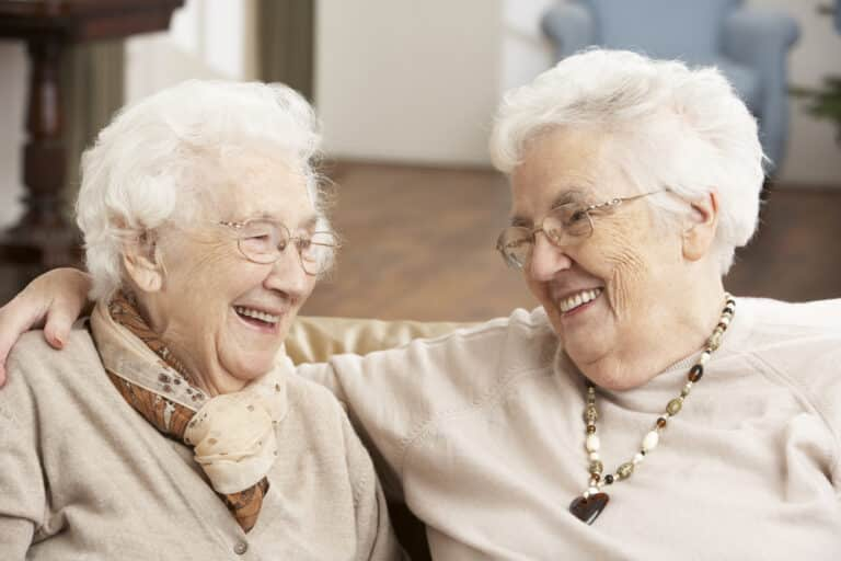 Two senior women smiling at each other