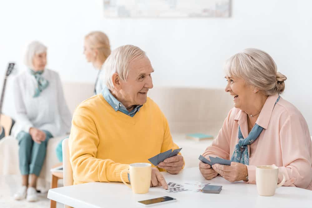 Smiling senior couple playing cards at a table