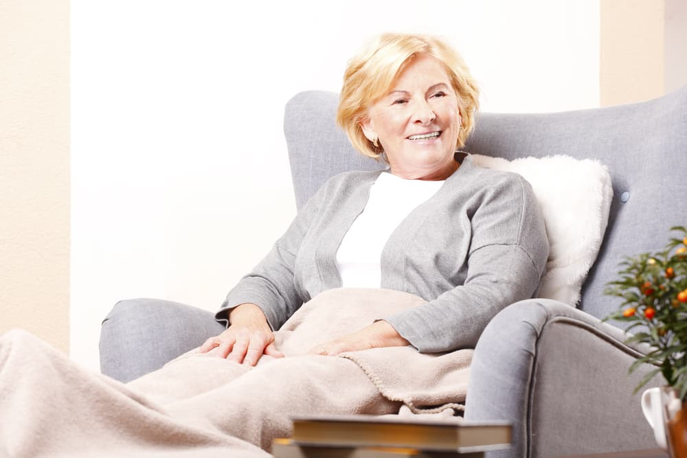 Senior woman smiling at home, sitting in armchair with blanket on her lap