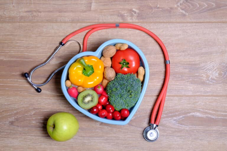 Healthy food in heart-shaped container on wood surface with stethoscope