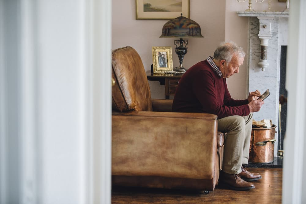 Senior man looking at photo while sitting in home