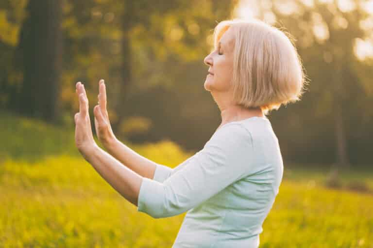 Senior woman in the early morning, outside, performing tai chi