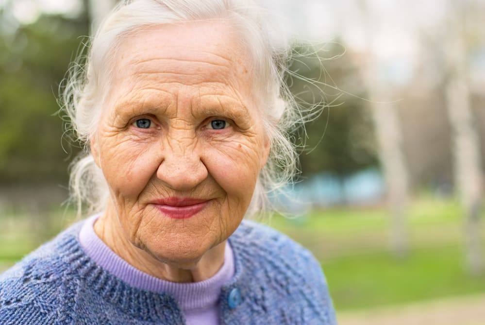 Close-up of senior woman smiling, outdoor background