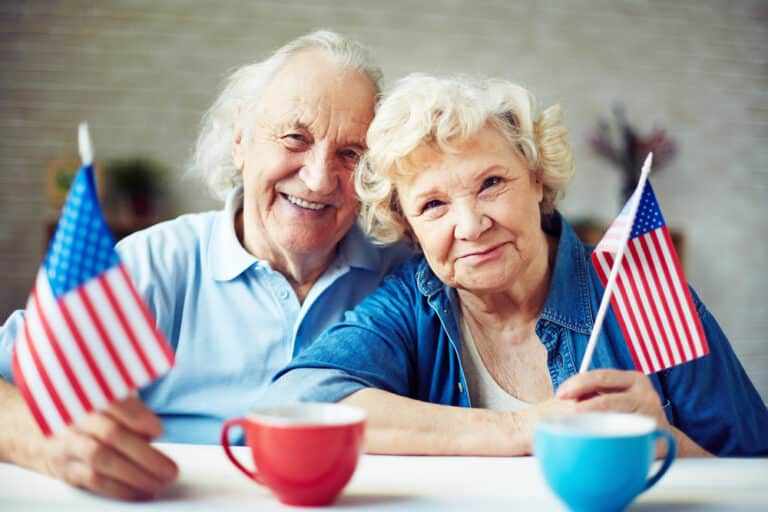 Senior couple holding american flags at kitchen table, mugs in foreground